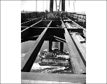 Looking down at the pier through the unfinished roadway of the Tacoma Narrows Bridge during...