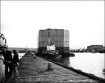 "Caisson for the Tacoma Narrows Bridge being towed in Salmon Bay by the tugboat ""Active"",..."