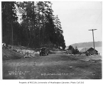 Construction workers building fish pond outlets with a view of the road along Lake Washington at...