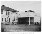 Juanita school being painted showing painters on scaffolding, Juanita, September 6, 1934