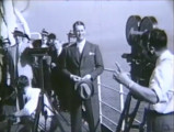 Maurice Chevalier poses for cameras on the deck of a ship, 1931