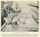 View on Scrape BoatShowing a scrape (the triangular iron frame with the mesh bag), a crate with...
