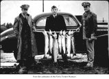 Navy personnel with fish and a van at Quillayute Naval Auxiliary Air Station
