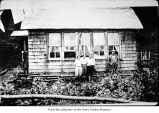 People posing outside a house, probably pioneers on the Olympic Peninsula