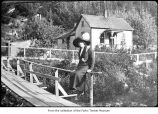 Women on a footbridge near a house, probably on the Olympic Peninsula