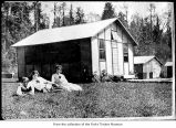 Women posing on a lawn outside cabins, probably on the Olympic Peninsula