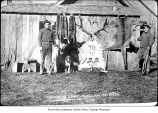 Trappers with hides and a dog outside a house, probably on the Olympic Peninsula