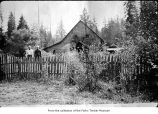 Two people outside a house, probably pioneers on the Olympic Peninsula