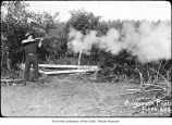 Man firing a rifle, probably on the Olympic Peninsula