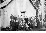 People posing outside a building, probably pioneers on the Olympic Peninsula