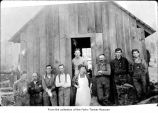 Men and a woman posing outside a small cabin, probably pioneers on the Olympic Peninsula