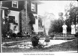Women in yard looking at a wading pool. This is the T. Rixon house located in Sappho, WA.