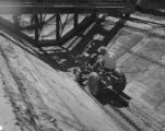 Construction worker following the grader in ditch on a small tractor, Grand Coulee Dam...