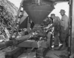 Two men examining engine rig with hopper and drive train, Grand Coulee construction site, ca....