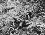 Exhausted Klondiker resting on the trail, probably Alaska, 1898.