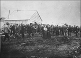 Crowd of men and women standing outside of post office, Nome, Alaska, ca. 1900.