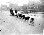 Three people with dogsled team in Dawson street, Alaska, ca. 1898.