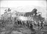 Crowds gathering at the ruins of the Opera House on Front St. after a fire, Dawson, Yukon...
