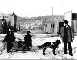 Dog hauling sled with woman and two children, Skagway, Alaska, ca. 1898.