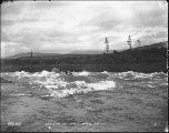 Small boat navigating the White Horse Rapids on the Yukon River, Yukon Territory, ca. 1898.