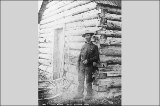 John F. Huston standing in front of log cabin, Alaska, ca. 1900.