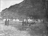 Ferrying people across the Klondike River in small boats, Dawson, Yukon Territory, ca. 1898.