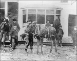 Street scene showing man standing with moose in harness, Skagway, Alaska March 22, 1900.