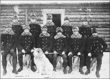 North-West Mounted Police posed for group picture in front of log cabin, Dawson, Yukon Territory,...