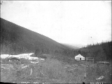 Log cabin and tent on Carmack's Fork on the north fork of Bonanza Creek, Yukon Territory, ca. 1898