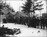 Line of men and women waiting to receive mail at the post office, Skagway, Alaska, ca. 1899.