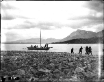 Men hauling scow along shore of Windy Arm, Tagish Lake, Yukon Territory, 1898.