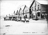 Dogsled team carrying food supplies outside the North American Transportation and Trading Co....