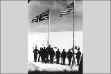 North-West Mounted Police standing next to American and British flags marking the boundary between...