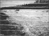 Small boat navigating the Whitehorse Rapids on the Yukon River, Yukon Territory, ca. 1898.
