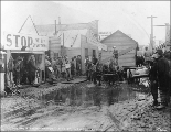 Moving a house with a team of horses through the mud down Front St., Nome, Alaska, August 27, 1900.