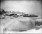 Loading freight and passengers onto lightering scow from the beach during winter, Nome, Alaska,...