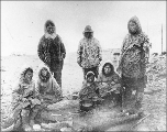 Eskimos wearing gut parkas gathered around campfire, Penny River, vicinity of Nome, Alaska, ca....