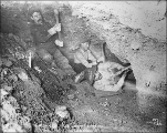 Three miners using pickaxes in underground gold mine lit by candlelight, Gold Hill, Yukon...