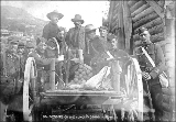 North-West Mounted Police officers carrying rifles guarding wagon loaded with gold, Yukon...