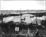 Boats and tents at the mouth of the Snake River, Nome, Alaska, ca. 1900.