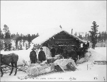 Klondikers with horse drawn sleds resting at a log cabin, White Pass Trail, ca. 1898.
