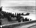 Passengers departing in a small boat from the Nome beach for a steamer waiting offshore, Alaska,...
