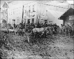 Horse drawn cart hauling lumber stuck in mud on Front St., Dawson, Yukon Territory, ca. 1899.