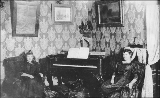 Two women seated next to piano in Esther Duffy's house, ca. 1898.