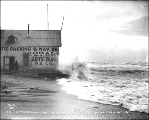 Waves breaking against Pacific Packing & Navigation Co. office on the beach during a storm of...