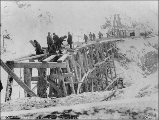 Crew working on wooden trestle bridge connecting Tunnel Mountain with the south portal of the...