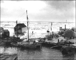 Waves washing houses off of the sand spit during a storm, Nome, Alaska, ca. 1902.