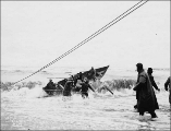 Attempting to launch a boat in the surf at Nome, Alaska, ca. 1900.