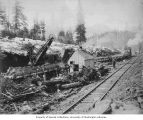 Steam shovel working at the gravel pit at Mile 6 showing railroad tracks and locomotive in the...