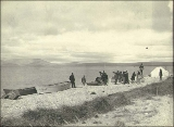 Boats, men and supplies on the beach at Port Clarence, Alaska, ca. 1900.